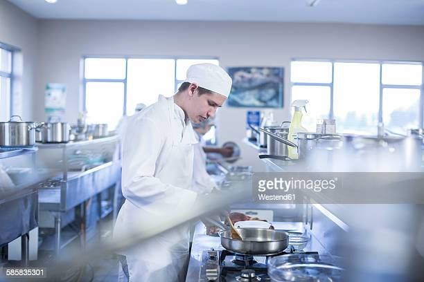Teenager cooking in canteen kitchen