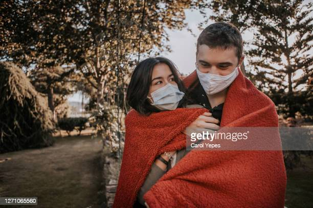 teenager couple embrancing outdoors with protective facial mask - kissing stock pictures, royalty-free photos & images