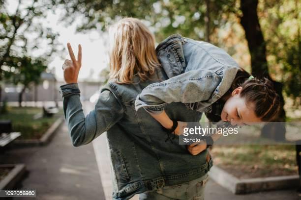teenager couple having fun in the public park - petit ami photos et images de collection
