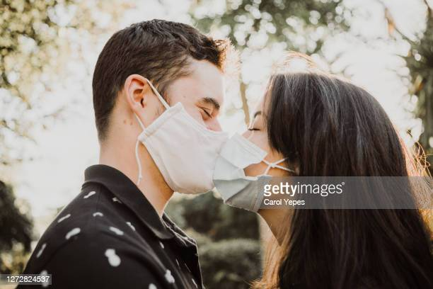 teenager couple kissing outdoors with protective facial mask - キス ストックフォトと画像