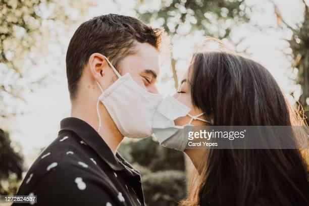 teenager couple kissing outdoors with protective facial mask - besar fotografías e imágenes de stock