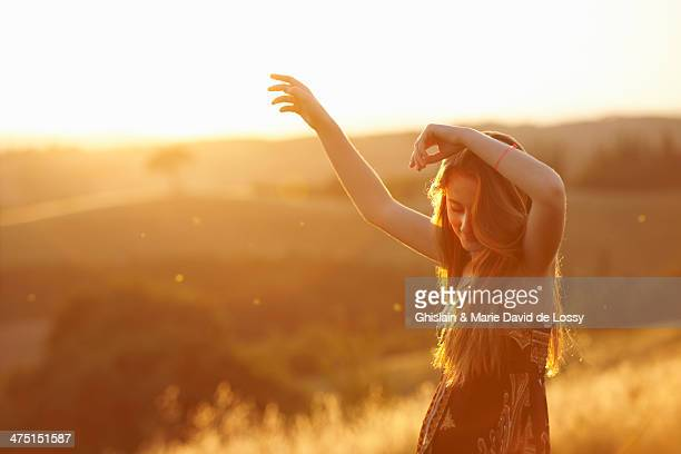 Teenager dancing in field at dusk