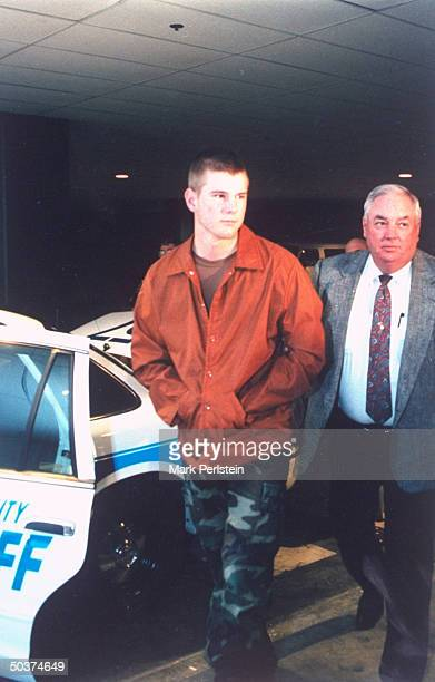 Teenager David Graham who murdered classmate Adrianne Jones at behest of his jealous girlfriend Diane Zamora standing w police in parking lot while...