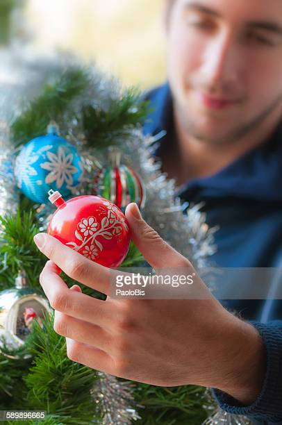 A teenager decorating Christmas tree