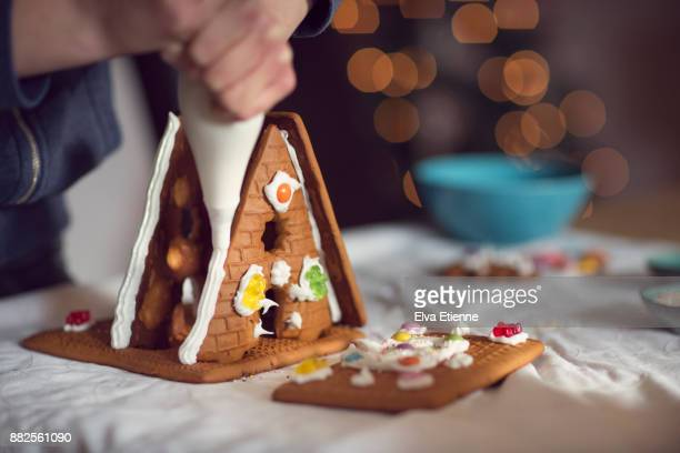 Teenager decorating gingerbread house