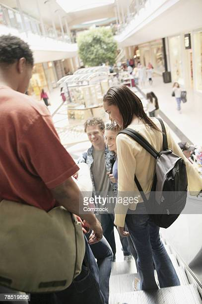 Teenager descending escalator in shopping mall