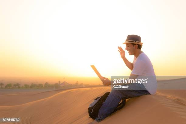 Teenager doing video conferencing from a desert