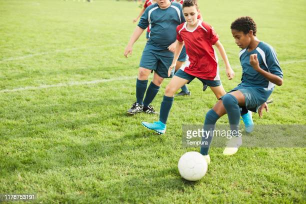 adolescent dribble ses adversaires lors d'un match de football. - club de football photos et images de collection