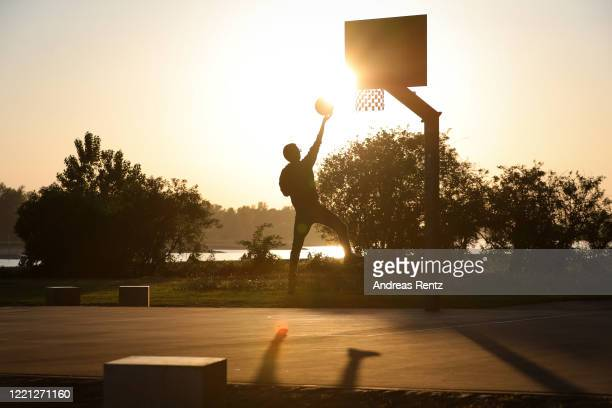 Teenager drives to the basketball hoop on a public court near the river Rhine at sunset during the novel coronavirus crisis on April 26, 2020 in...