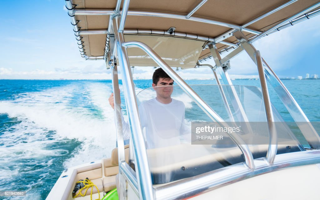 Teenager driving a boat : Stock Photo