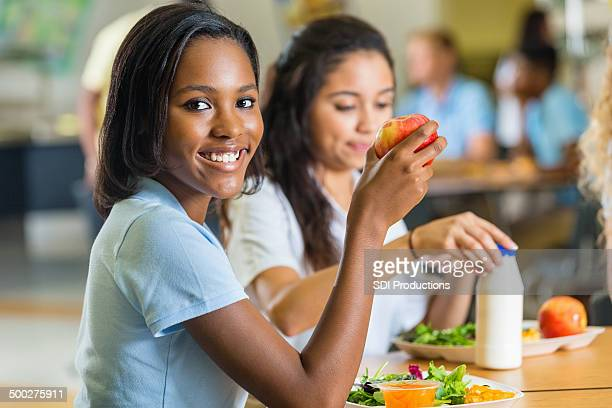 Teenager eating healthy lunch with friends in school lunchroom