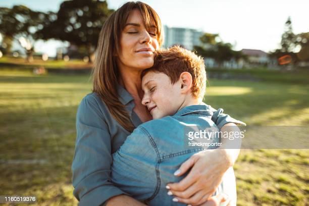 tonåring omfamnade med mamma tröska hennes son - son bildbanksfoton och bilder