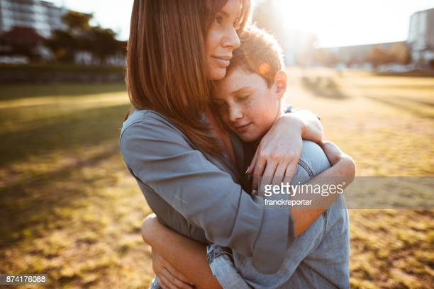 teenager embraced with mom consoling her son - embracing stock pictures, royalty-free photos & images