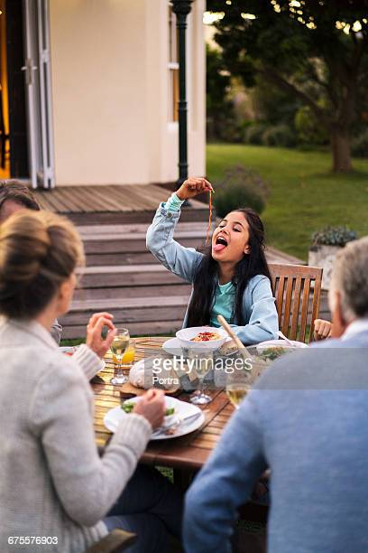 Teenager enjoying food while sitting with family