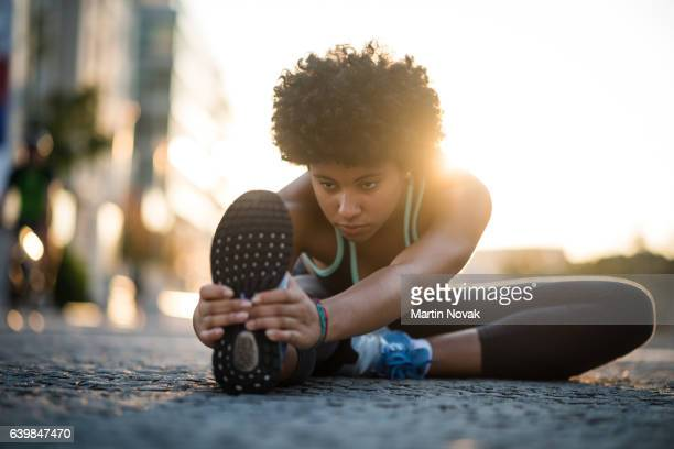 Teenager exercises in city at sunset