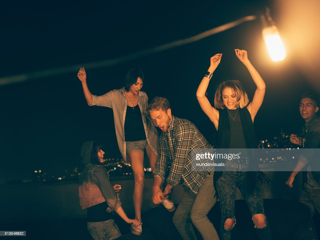Teenager friends dancing and laughing on a rooftop party : Stock Photo