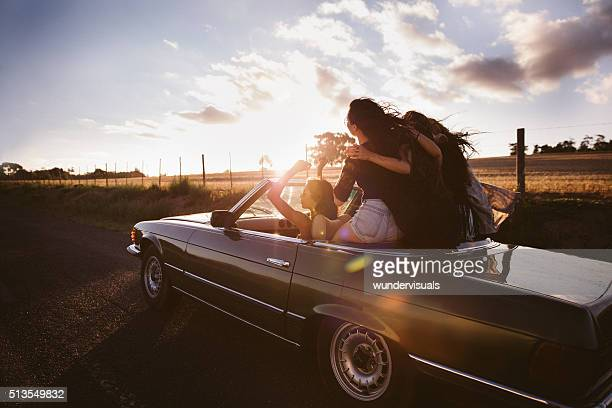 Teenager friends embracing joyfully on their road trip at sunset