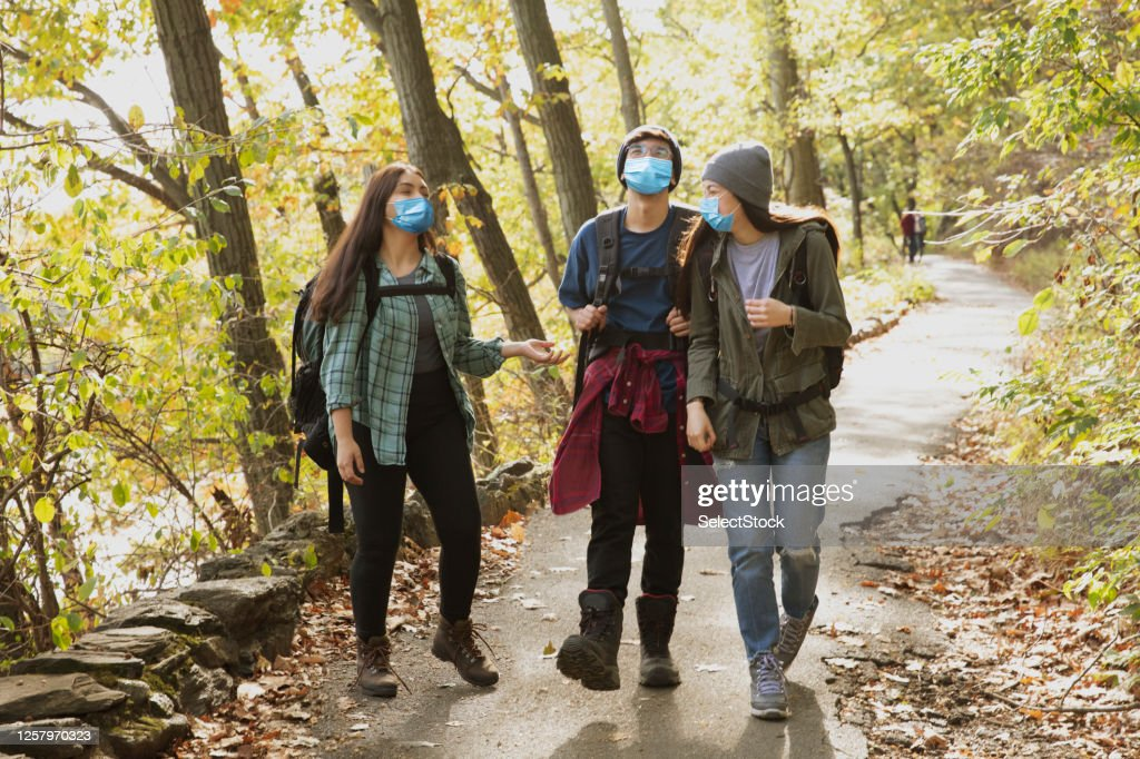 Teenager friends hiking outside in nature wearing mask : Stock Photo