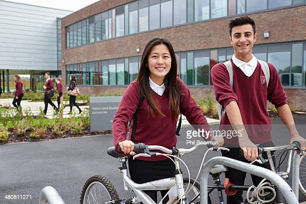 Teenager friends with cycles outside school