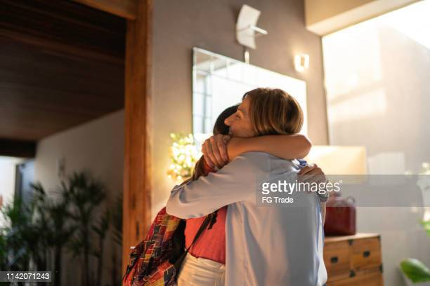 teenager gilr and mature woman embracing - arrival stock pictures, royalty-free photos & images