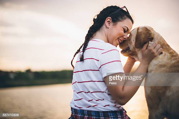 Teenager girl and her dog enjoying in golden sunset