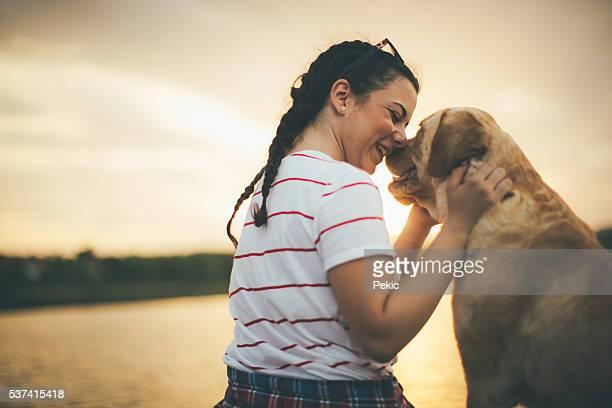 Chica adolescente y su perro disfrutar en puesta de sol de oro