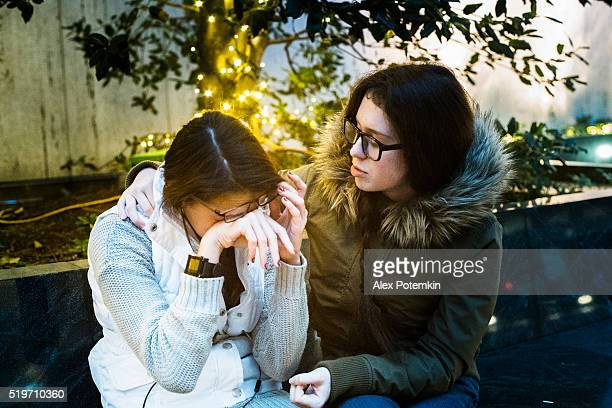Teenager girl crying and other sister comforting her
