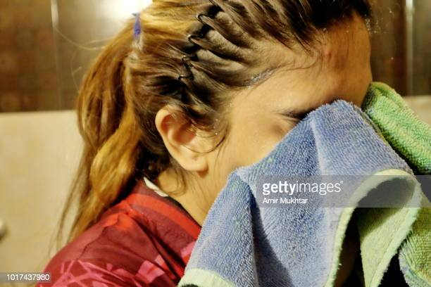 a teenager girl drying her face with towel - amir mukhtar stock photos and pictures