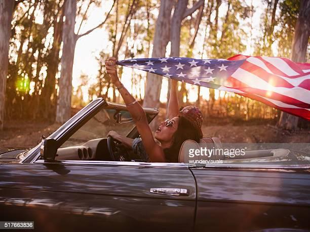 Adolescente Chica sosteniendo una bandera estadounidense en un viaje por carretera