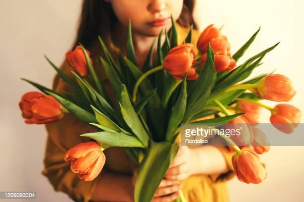 teenager girl in a yellow mustard dress with a bouquet of orange tulips in her hands - muttertag blumen stock-fotos und bilder