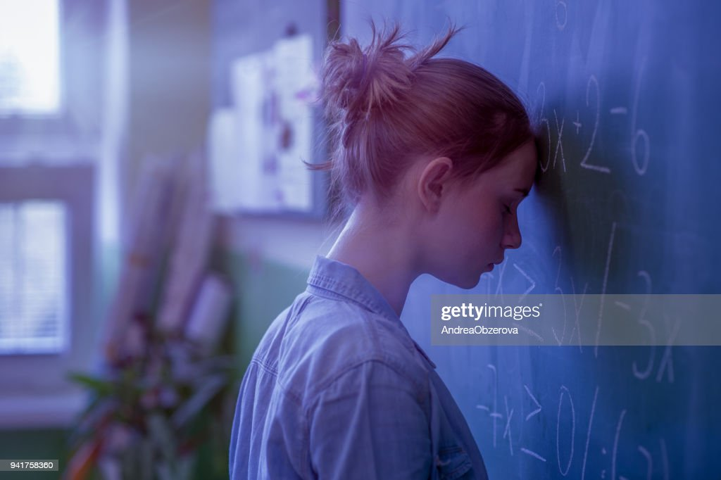 Teenager girl in math class overwhelmed by the math formula. Pressure, Education, Success concept. : Foto de stock