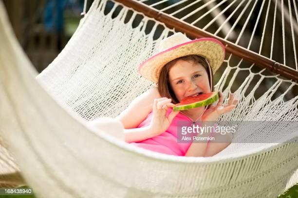 Teenager-Mädchen im Stroh Hut Essen Wassermelone auf Hängematte