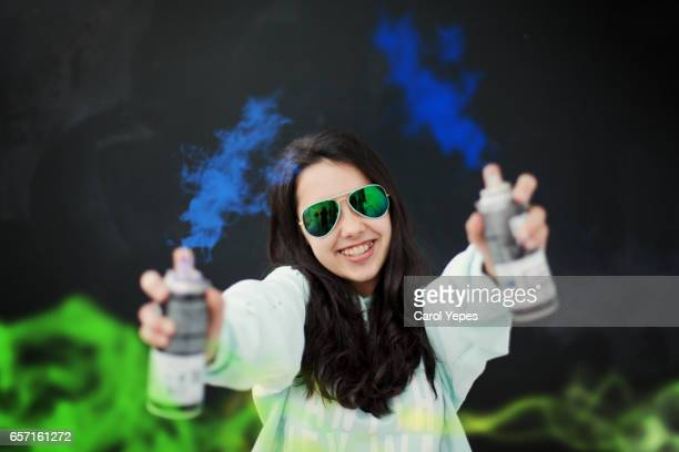 teenager girl in sunglasses with aerosol paint