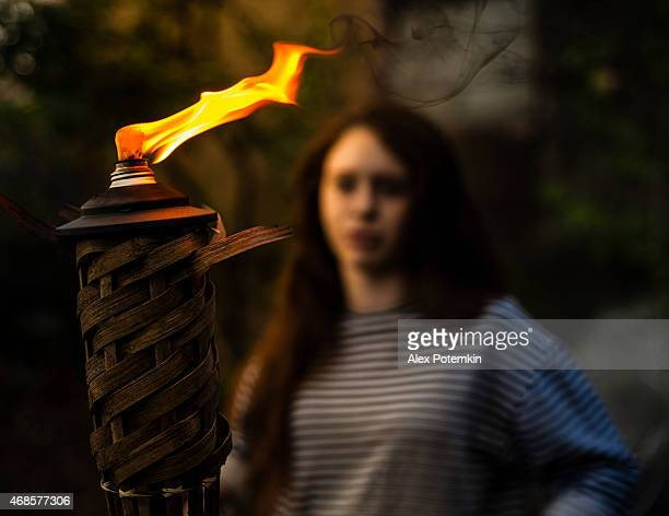 Teenager girl in the garden with flaming torch
