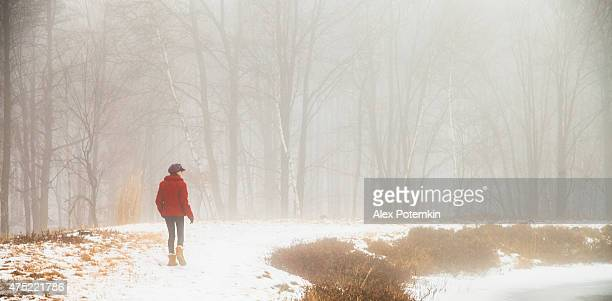 teenager girl in the red coat walking around the lake - pocono mountains stock pictures, royalty-free photos & images