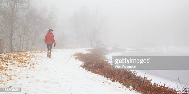 Teenager girl in the red coat walking around the lake