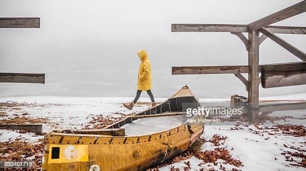 Teenager girl in the yellow coat walking around the lake