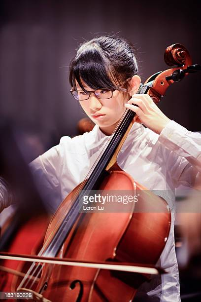 Teenager girl is playing cello in a concert
