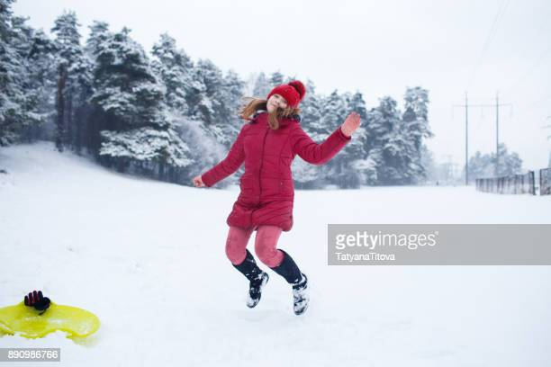 Teenager girl jumping on winter snow background