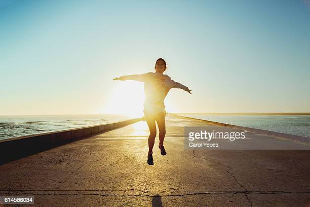teenager girl jumping outdoors at sunset - flying stock photos and pictures