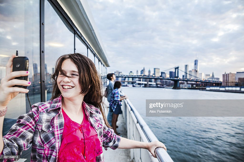 Teenager girl make selfie at ferry in front of Manhattan : Stock Photo