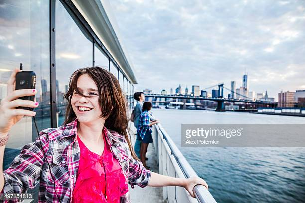 Teenager girl make selfie at ferry in front of Manhattan