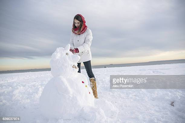Teenager girl make the snowman at the beach