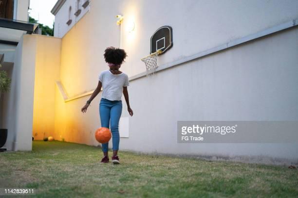 tiener meisje spelen doen kick-ups in de achtertuin - schoppen lichaamsbeweging stockfoto's en -beelden