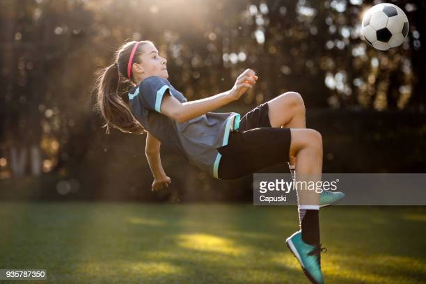 teenager girl playing soccer - kicking stock pictures, royalty-free photos & images