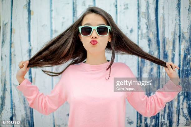 teenager girl playing with hair with fun expression - adolescente imagens e fotografias de stock