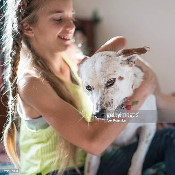Teenager girl playing with the dog