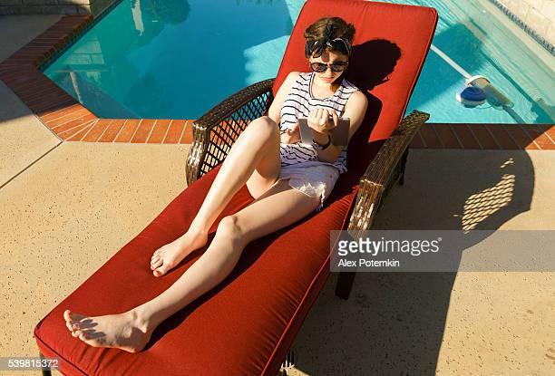 Teenager girl reading tablet sitting in shezlong near backyard's pool