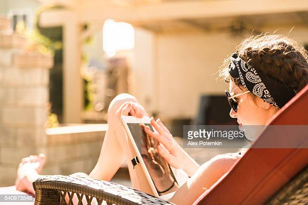 teenager girl reading tablet while sitting in shezlong on backyard - girls sunbathing stock pictures, royalty-free photos & images