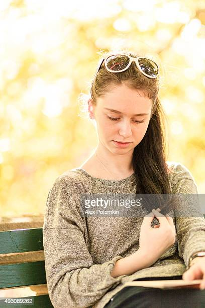 Teenager girl reading the book in the park at fall